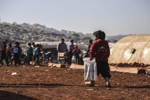 A child carrying a Unicef plastic bag walks towards a class inside a tent at Reyyan Camp in Kafr Uruq village of Idlib, Syria on 24 November 2020. [Muhammed Abdullah - Anadolu Agency]