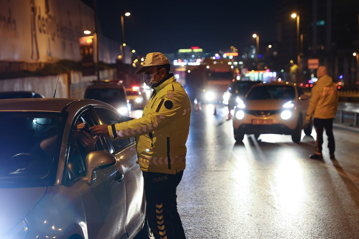 A police officer stops vehicles to check for permission at D-100 Highway after a general curfew imposed every weeknight from 9 pm to 5 am within new measures against a second wave of the COVID-19 pandemic, Istanbul, Turkey on December 08, 2020 [Arif Hüdaverdi Yaman/Anadolu Agency]