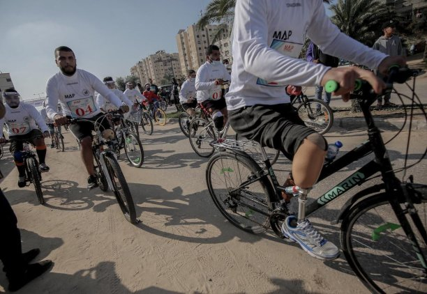Dozens of Palestinians who lost their legs in Israeli attacks on the Strip participated in a cycling race organised by the Rehabilitation and Social Training Association in cooperation with the Medical Aid Society in the Nuseirat refugee camp on 21 December 2020 [Mohammed Asad/Middle East Monitor]