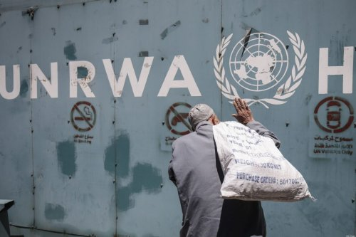 A Palestinian man stands in front of the emblem of the UN Relief and Works Agency for Palestine Refugees in the Near East (UNRWA) in Gaza City on 31 July 2018 [SAID KHATIB/AFP/Getty Images]