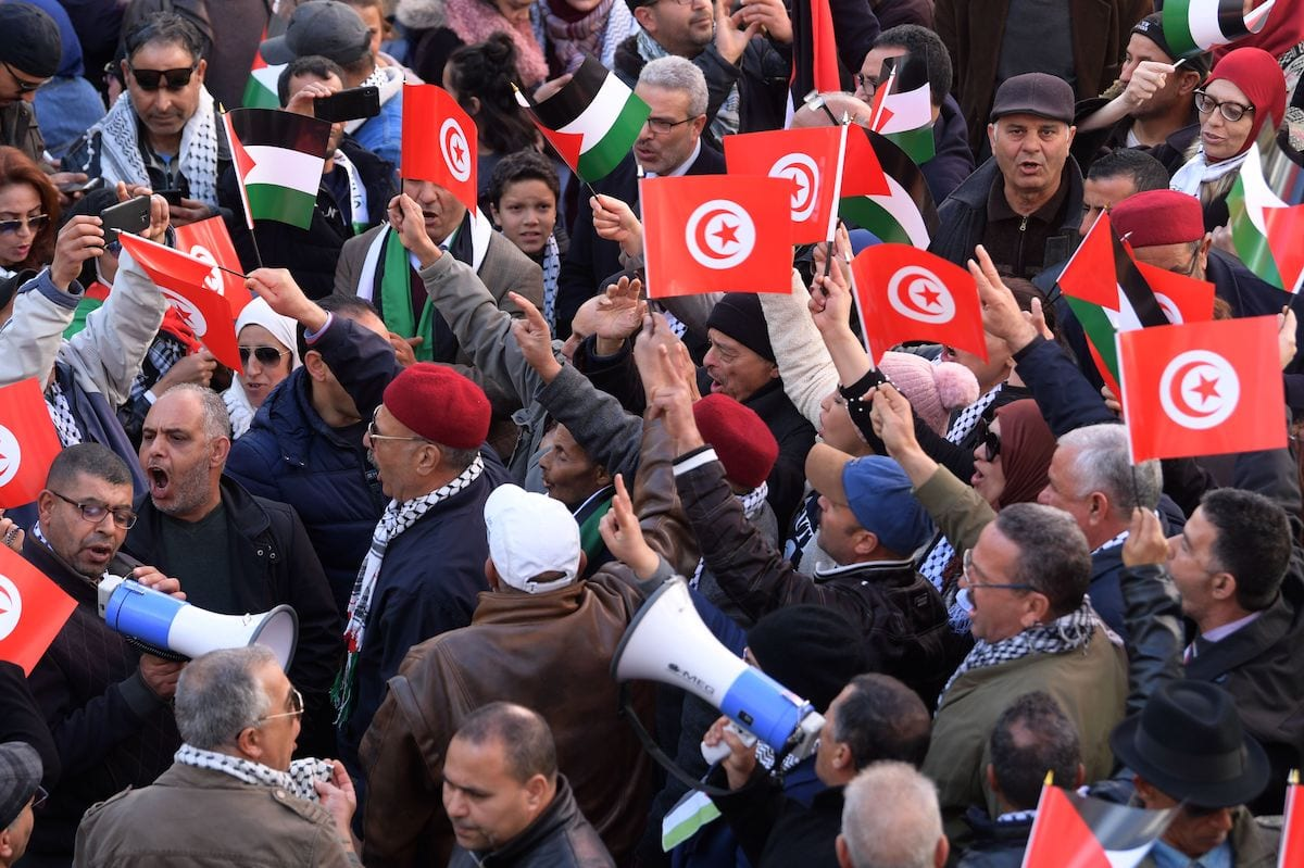 Tunisian demonstrators wave Palestinian and national (red) flags during a protest against US President Donald Trump's Middle East peace plan proposal on 5 February 2020 in Tunis. [FETHI BELAID/AFP via Getty Images]