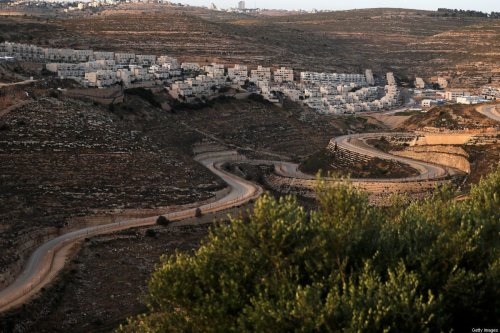 A serpentine road extends between the Jewish settlement of Givat Zeev (background) and Palestinian villages near the Israeli-occupied West Bank city of Ramallah, on June 10, 2020 [AHMAD GHARABLI/AFP via Getty Images]
