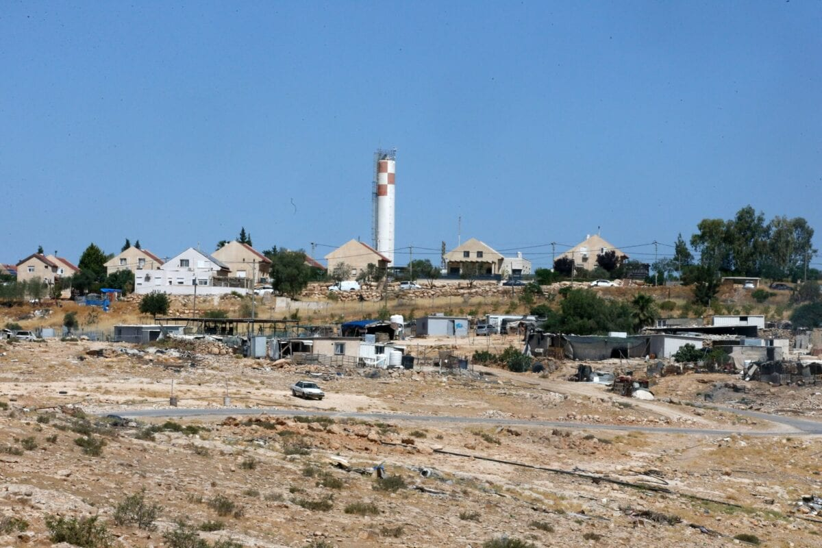 """Tents and shacks used as habitats by Palestinians are pictured in the village of Um al-Kheir in """"area C"""", in front of the Jewish settlement of Karmiel, near the occupied West Bank city of Hebron, on June 14, 2020. - Israel intends to annex West Bank settlements and the Jordan Valley, as proposed by US President Donald Trump, with initial steps slated to begin from July 1. """"Area C"""" is a stretch of land accounting for 60 percent of the West Bank over which Israel has control under the terms of the Oslo Accords signed between Israel and the Palestinians in the 1990s. It is extremely difficult for Palestinians to receive building permits from Israeli authorities for that area. (Photo by HAZEM BADER / AFP) (Photo by HAZEM BADER/AFP via Getty Images)"""