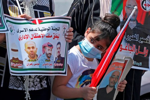 A Palestinian girl wearing a protective mask holds a picture of a Palestinian prisoner during a protest to show their support to prisoners held in Israeli jails, outside the offices of the International Committee of the Red Cross in the West Bank city of Nablus on August 26, 2020. - The UAE's decision to normalise ties with Israel has been welcomed by some Arab countries, but despite cheerleading from the US, others, including the Palestinians, have rejected the idea. Many Palestinians saw the move as a betrayal of their cause by the Gulf country. (Photo by JAAFAR ASHTIYEH / AFP) (Photo by JAAFAR ASHTIYEH/AFP via Getty Images)