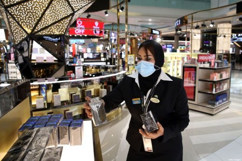 A duty-free employee, wearing a protective face mask due to the Covid-19 pandemic, restocks a shelf at the Muscat international airport in the Omani capital on October 1, 2020 [MOHAMMED MAHJOUB/AFP via Getty Images]
