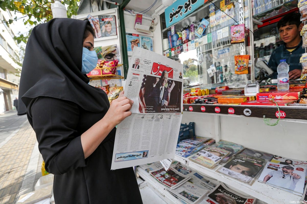 A woman browses a copy of Iranian Farsi newspaper Shargh featuring the 2020 US general election results at a news stand in Iran's capital Tehran on November 8, 2020. (Photo by ATTA KENARE / AFP) (Photo by ATTA KENARE/AFP via Getty Images)