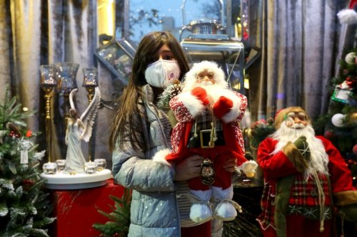 An Iranian girl, wearing a protective face mask, carries a stuffed Santa toy outside a shop selling Christmas decorations in the capital Tehran on December 22, 2020 [ATTA KENARE/AFP via Getty Images]