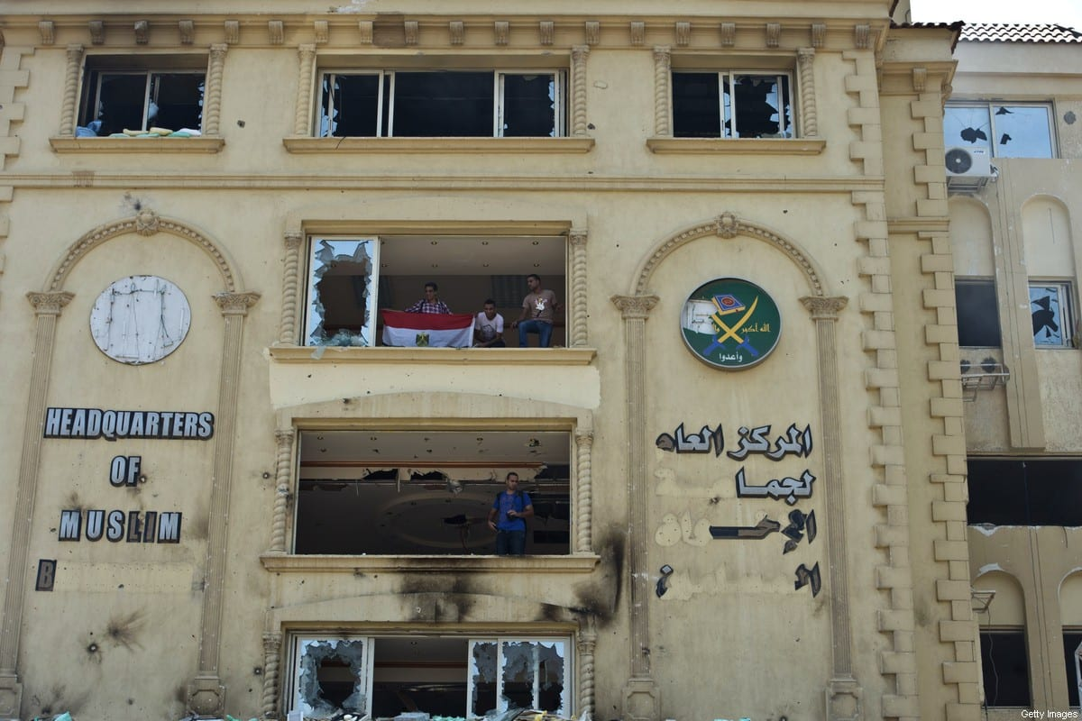 Egyptian protesters stand in the burnt headquarters of the Muslim Brotherhood in the Moqattam district of Cairo on July 1, 2013 [KHALED DESOUKI/AFP via Getty Images]