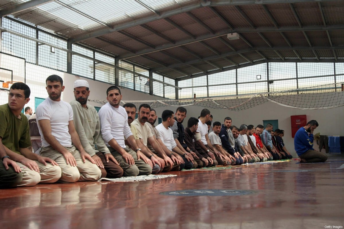 GILBOA PRISON, Israel: Palestinian prisoners kneel in a gym as they take part in prayers 05 March 2006 at the Gilboa prison, east of the northern Israeli town of Afula. Most of the 850 adult male prisoners in this prison are serving very long jail terms and some are serving life sentences for taking part in militant acts. AFP PHOTO/Hagai AHARON-ISRAEL OUT (Photo credit should read HAGAI AHARON/AFP via Getty Images)
