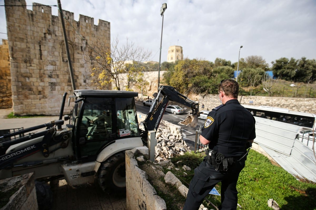 The Israeli-run Jerusalem Municipality team along with Israeli soldiers and bulldozers demolish the wall and staircase in the northern part of the Al-Yusufiye Cemetery to make a garden in the area, in Jerusalem on 14 December 2020. [Mostafa Alkharouf - Anadolu Agency]