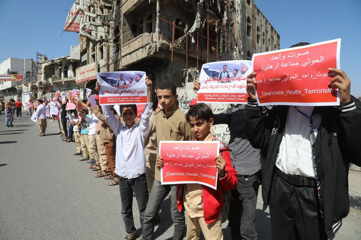 """Yemenis hold placards during a protest to demand Iran-backed Houthis to be listed as a """" terror organization"""" at a stadium in Taiz, Yemen on 13 December 2020. [Abdulnasser Alseddik - Anadolu Agency]"""