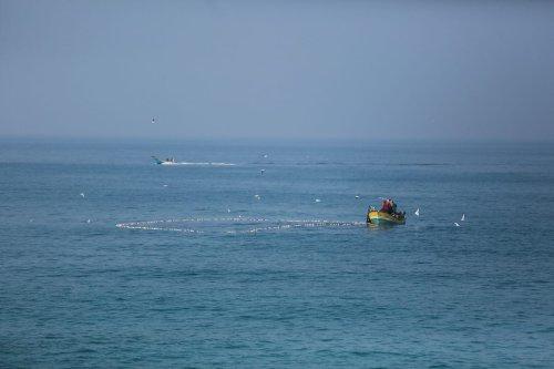 GAZA CITY, GAZA - JANUARY 04: Palestinian fishermen, hunting in the blockaded Gaza Strip, collect their nets on the Gaza City coast on January 04, 2021. ( Mustafa Hassona - Anadolu Agency )