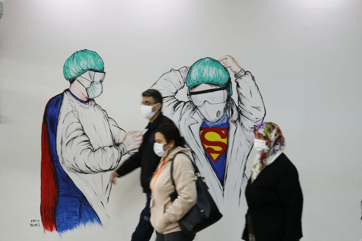 """People in face masks walk past a mural of a doctor and a nurse wearing """"superman"""" costumes, dedicated to healthcare personnel at the forefront coronavirus pandemic, at Adnan Menderes University (ADU) hospital in Aydin, Turkey on January 9, 2021 [Ferdi Uzun / Anadolu Agency]"""