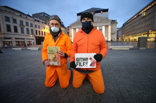 People wearing prisoners' uniform protest to demand for the closure of Guantanamo on the 19th anniversary of its opening in Brussels City Center, Belgium, on January 11, 2021 [Dursun Aydemir / Anadolu Agency]