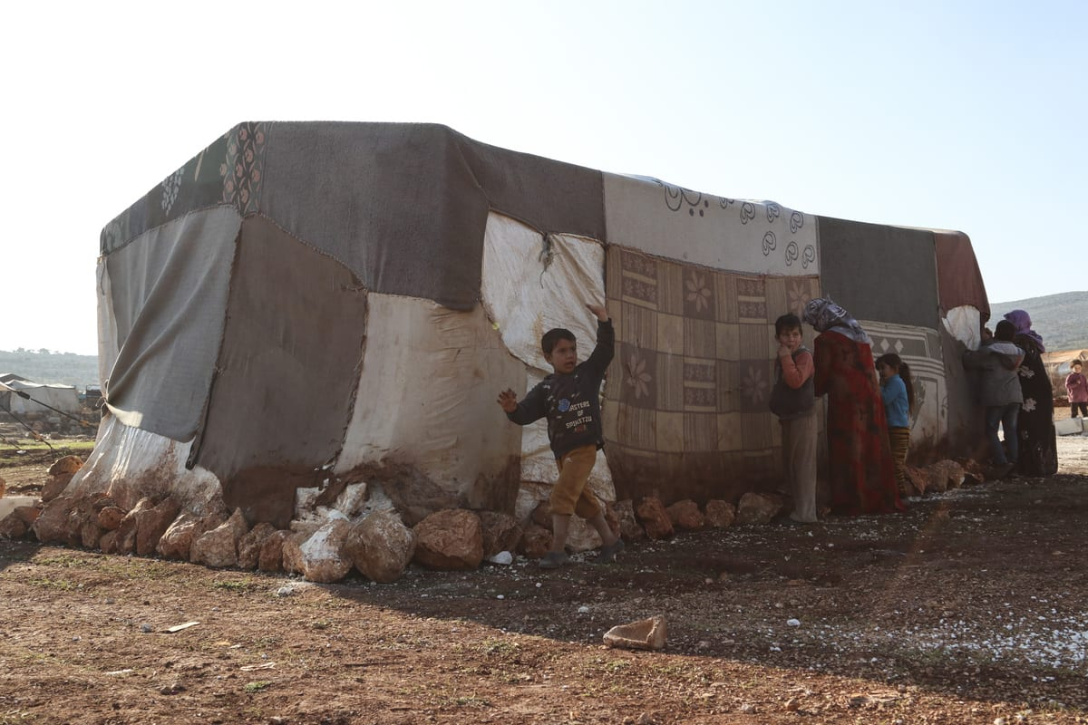 IDLIB, SYRIA - DECEMBER 29: Syrian women fix tents damaged due to winter conditions with needle and thread to strengthen them against cold and rain at a refugee camp in Idlib, Syria on December 29, 2020. ( Muhammed Abdullah - Anadolu Agency )