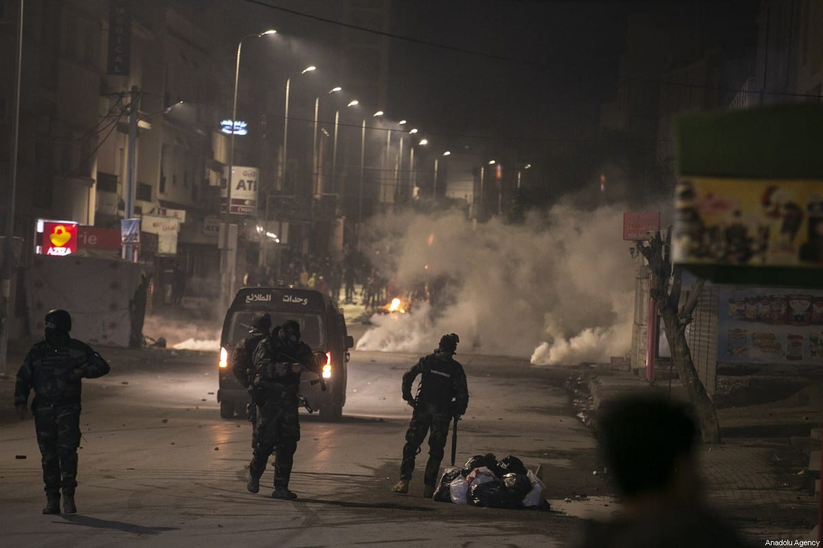 Tunisian protestors clash with police officers as they violate the curfew imposed to stem the coronavirus pandemic, during a protest against living conditions and unemployment at At-Tadaman district in the capital Tunis, Tunisia on January 15, 2021 [Yassine Gaidi / Anadolu Agency]