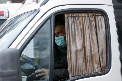 A Palestinian bus driver wears a protective mask amid fears of the spread of the coronavirus, in the West Bank on 7 March 2020 [HAZEM BADER/AFP/Getty Images]