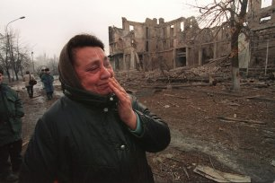 A Chechen woman cries as she walks past buildings that were destroyed during combats between Russian troops and Chechen soldiers in Grozny, Russia on on 28 December 1994 [HECTOR MATA/AFP/Getty Images]