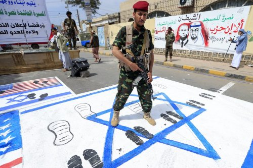 A fighter loyal to Yemen's Huthi rebels treads on US and Israeli flags painted on the ground during a rally in the capital Sanaa, on 22 August 2020, to protest the US-brokered deal to normalise Emirati-Israeli relations. [MOHAMMED HUWAIS/AFP via Getty Images]