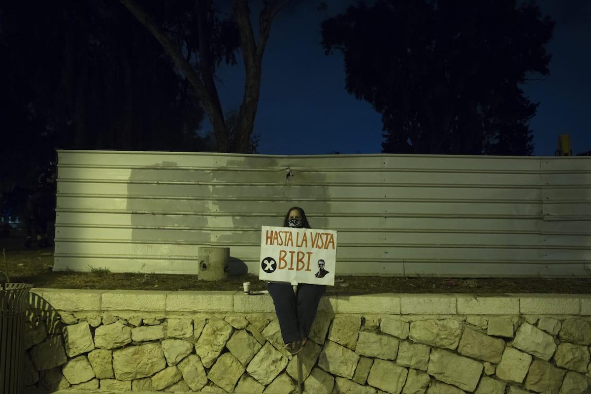 A protester holds a sign during a demonstration against Israeli Prime Minister Benjamin Netanyahu on October 31, 2020 in Jerusalem, Israel [Amir Levy/Getty Images]