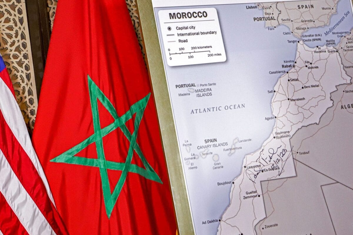 This picture taken on December 12, 2020 shows (L to R) US and Moroccan flags next to a US State Department-authorised map of Morocco recognising the internationally-disputed territory of the Western Sahara (bearing a signature by US Ambassador to Morocco David T. Fischer) as a part of the North African kingdom, in Morocco's capital Rabat. (Photo by - / AFP) (Photo by -/AFP via Getty Images)