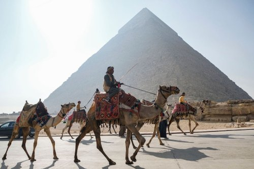 Camel trainers ride camels awaiting tourists by the Pyramid of Khafra (Chephren) at the Giza Pyramids Necropolis on the western outskirts of the Egyptian capital's twin city of Giza on 7 January 2021. [AMIR MAKAR/AFP via Getty Images]