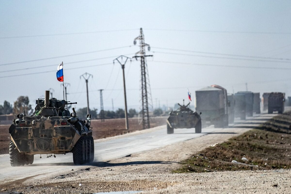 Russian troops escort a convoy of Syrian civilians leaving the town of Tal Tamr in the northeastern Hasakeh province, as they return to their homes in the northern town of Ain Issa in the countryside of the Raqqa region, via the strategic M4 highway, on January 10, 2021. - The town of Tal Tamr is on the front line between the Syrian Democratic Forces (SDF) and the Syrian factions supported by Turkey. Civilians stranded on both sides of the line because of heavy fighting, have been able to return to their homes during the past few days. (Photo by Delil SOULEIMAN / AFP) (Photo by DELIL SOULEIMAN/AFP via Getty Images)