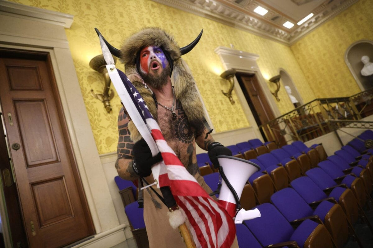 "A protester screams ""Freedom"" inside the Senate chamber after the U.S. Capitol was breached by a mob during a joint session of Congress on January 06, 2021 in Washington, DC [Win McNamee/Getty Images]"