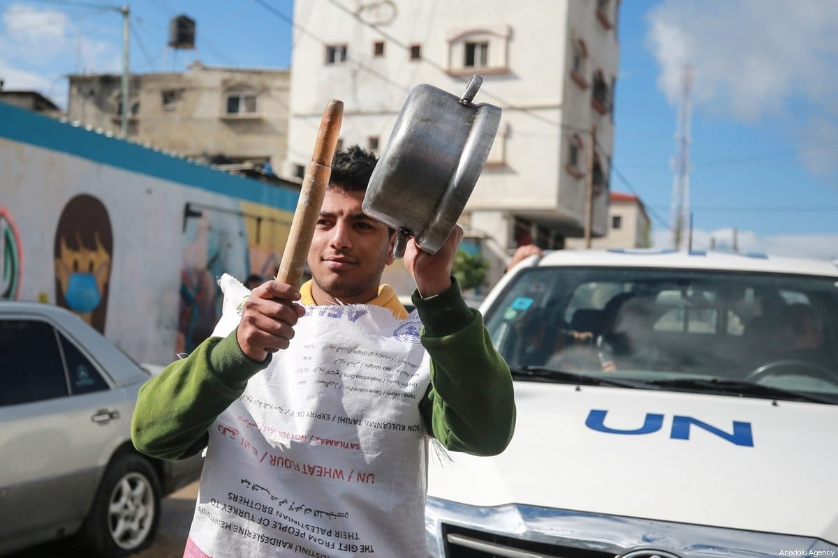 Palestinians hold placards as they gather during a protest against food aid cuts by the United Nations Relief and Works Agency (UNRWA), outside the UNRWA in Khan Yunis, Gaza on 20 January 2021. [Mustafa Hassona - Anadolu Agency]