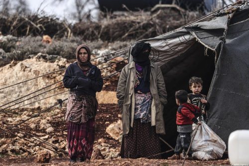 Syrians outside their makeshift tents in Turkey on 18 January 2021 [Metin Aktaş/Anadolu Agency]