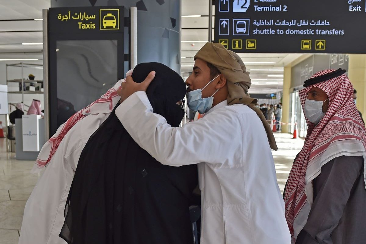 A man hugs his sister who arrived at King Khalid International Airport in the Saudi capital Riyadh on the first commercial flight from Qatar, on January 11, 2021 [FAYEZ NURELDINE/AFP via Getty Images]