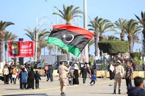 A soldier waves Libyan flag as people celebrate Libyan Revolution, known as the 17 February Revolution, which ousted former ruler Muammar Gaddafi, at the Martyrs' Square in Tripoli, Libya on 16 February 2021. [Hazem Turkia - Anadolu Agency]