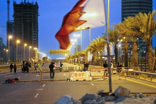 Bahraini anti-government protesters place concrete roadblocks on the highway leading to Pearl Square in Manama on 14 March 2011. [JAMES LAWLER DUGGAN/AFP via Getty Images]