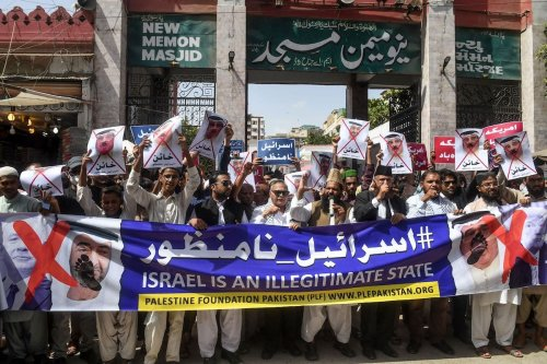Demonstrators carry a banner showing crossed-out portraits of Israel's Prime Minister Benjamin Netanyahu (L on banner), Abu Dhabi Crown Prince Sheikh Mohammed bin Zayed Al Nahyan (2L), Bahrain's King Hamad bin Isa al-Khalifa (2R) and US President Donald Trump (R) during a protest in the Pakistan's port city of Karachi on 25 September 2020, to denounce the Israeli normalisation deals with the United Arab Emirates and Bahrain. [ASIF HASSAN/AFP via Getty Images]