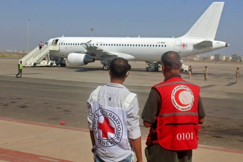 International Committee of the Red Cross (ICRC) and a Red Crescent volunteer look at an Airbus A320 aircraft at an airport in Yemen's southern city of Aden, the interim seat of the Yemeni government, on October 16, 2020, as the war-torn country began swapping 1,000 prisoners in a complex operation overseen by the International Committee of the Red Cross. - Over 170 former prisoners of war were freed today on the second day of a landmark exchange between war-torn Yemen's government and Huthi rebels, the International Committee of the Red Cross said. A plane from the southern city of Aden, the interim seat of the Yemeni government, took 101 former prisoners to the rebel-held capital Sanaa, while another aircraft transported 76 detainees in the opposite direction, the ICRC said on Twitter. (Photo by Saleh Al-OBEIDI / AFP) (Photo by SALEH AL-OBEIDI/AFP via Getty Images)