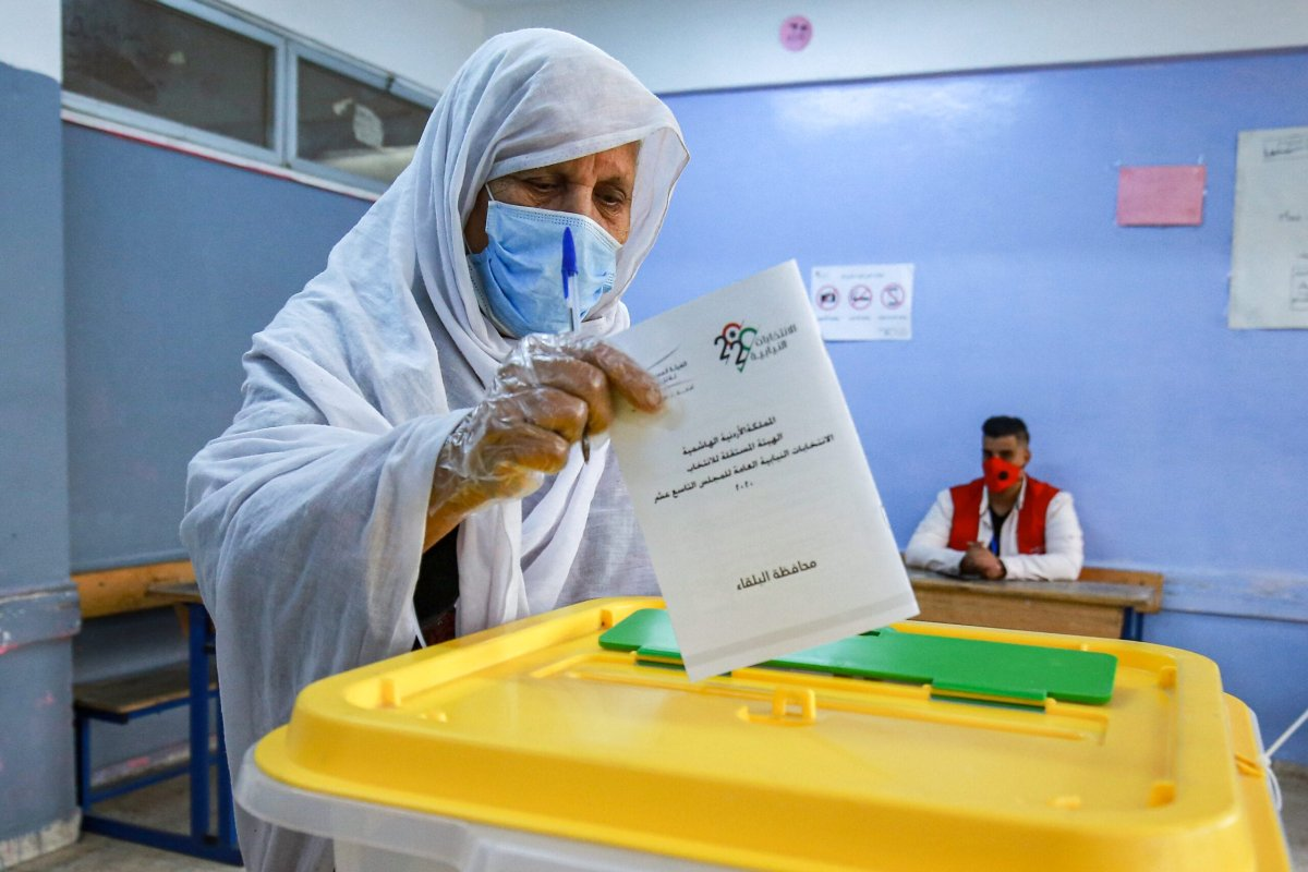An Palestinian elderly voter casts a ballot at a polling station on November 10, 2020 [KHALIL MAZRAAWI/afp/AFP via Getty Images]