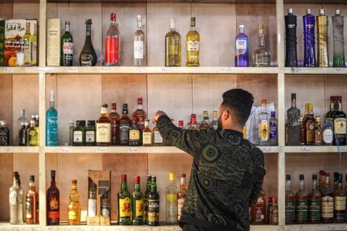 A shopworker arranges whisky bottles on a shelf at a liquor ship in the Bataween district in the centre of Iraq's capital Baghdad on 5 December 2020. [AYMAN HENNA/AFP via Getty Images]