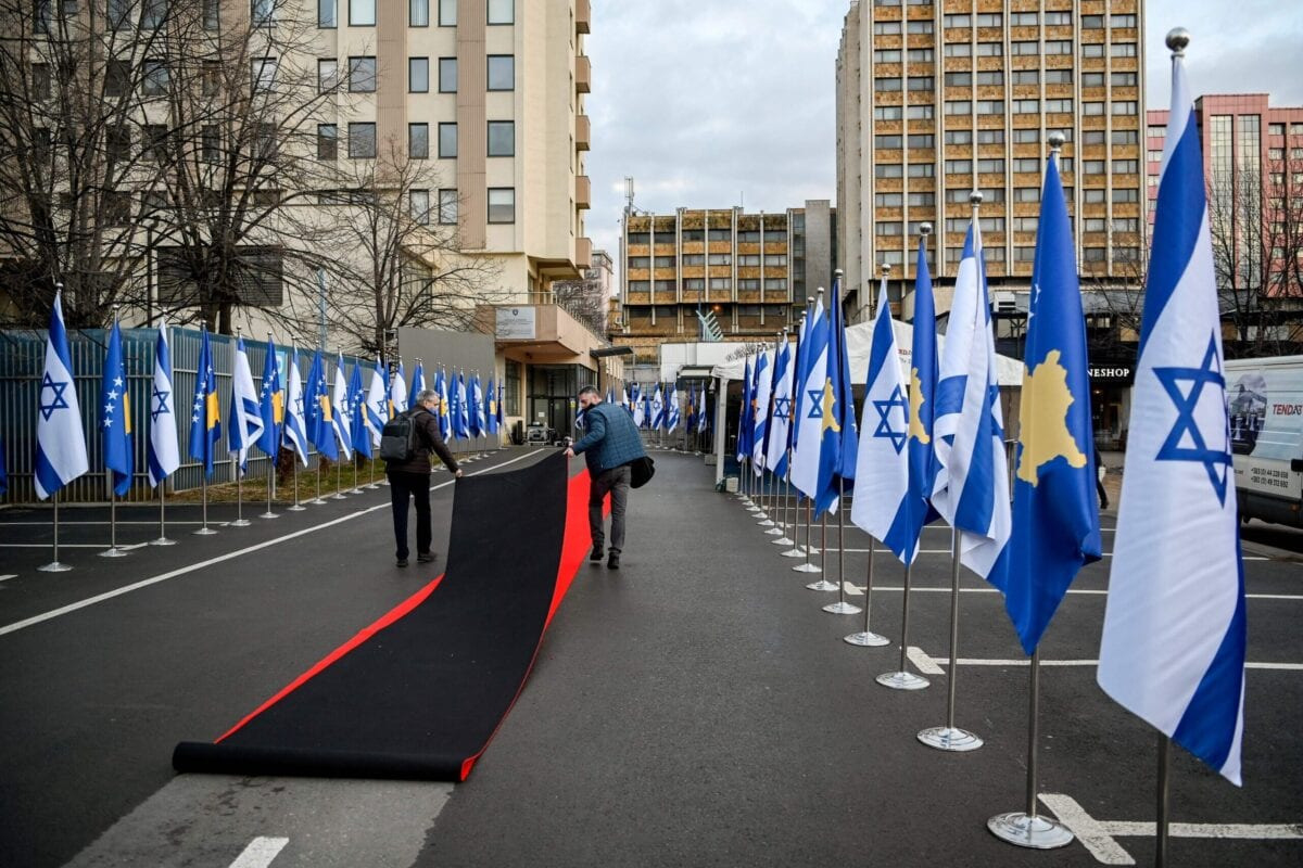 Workers drag the red carpet next to Kosovo's and Israel's flags displayed during a ceremony at the headquarters of the Foreign Ministry in Pristina on February 1, 2021. - Kosovo and Israel established diplomatic ties on February 1, 2021, with the Muslim-majority territory recognising Jerusalem as the Jewish state's capital, putting it at odds with the rest of the Islamic world. In a ceremony held over Zoom in Jerusalem and Pristina, Israeli Foreign Minister and his counterpart from Kosovo signed a joint declaration establishing ties. (Photo by Armend NIMANI / AFP) (Photo by ARMEND NIMANI/AFP via Getty Images)