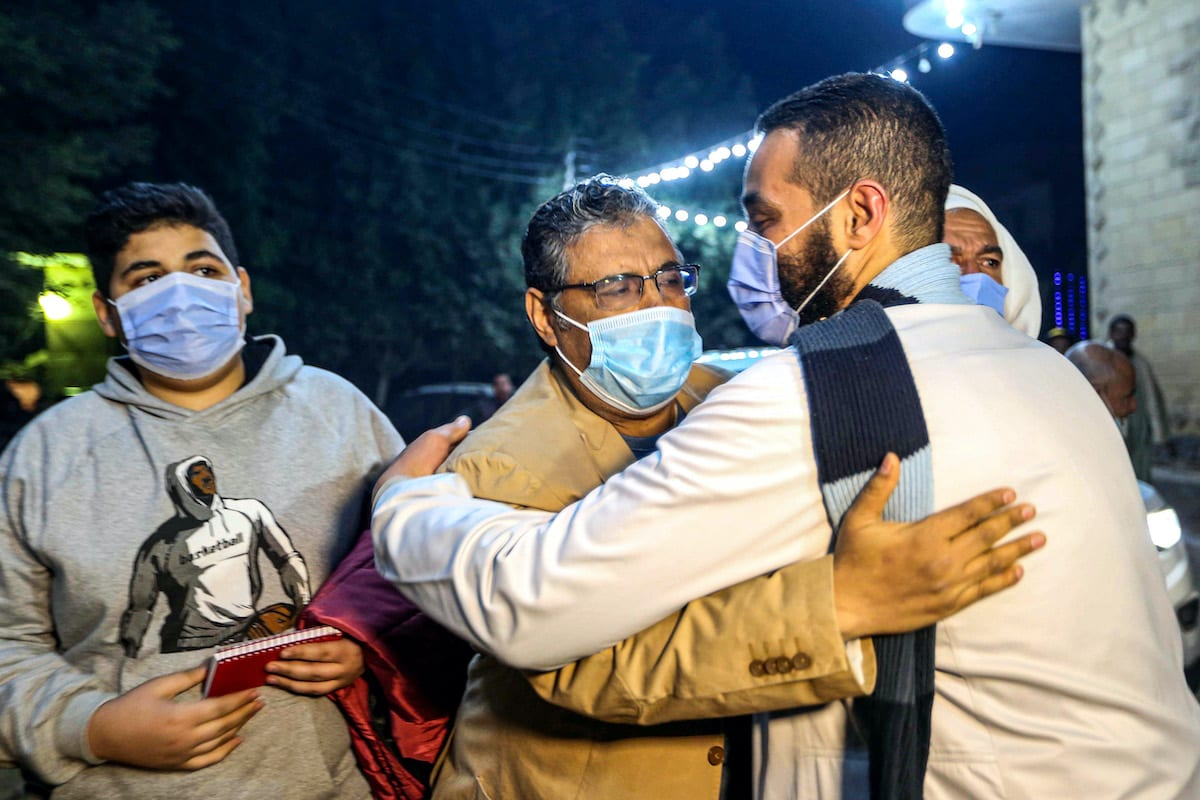 Mahmoud Hussein (C), an Egyptian national and senior journalist for Qatar-based Al Jazeera Arabic, is embraced by a man upon his arrival at his family home in the Giza village of Zawyet Abu Musallam, about 30 kilometres south of Egypt's capital Cairo on 6 February 2021 upon his release from detention. [AFP via Getty Images]