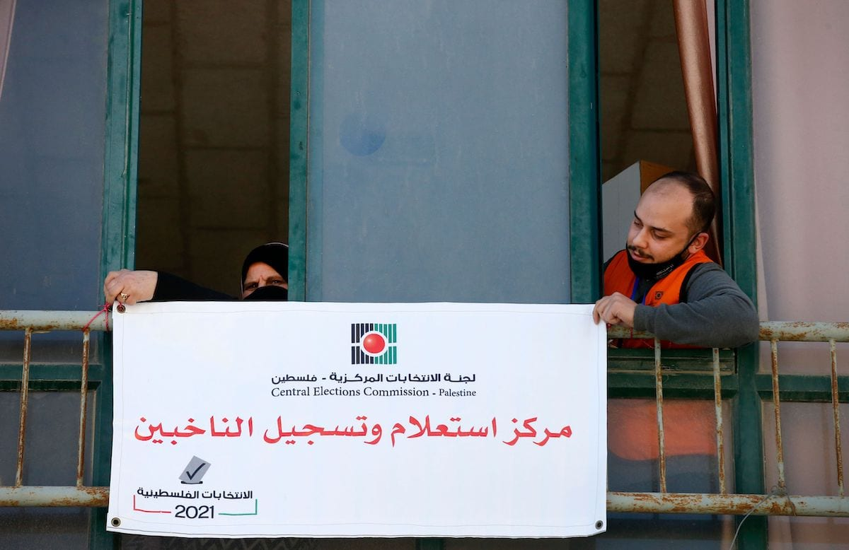 """Members of the Palestinian Central Elections Commission hang a sign reading in Arabic """"voter information and registration centre"""" in the West Bank town of Hebron on 10 February 2021. [HAZEM BADER/AFP via Getty Images]"""