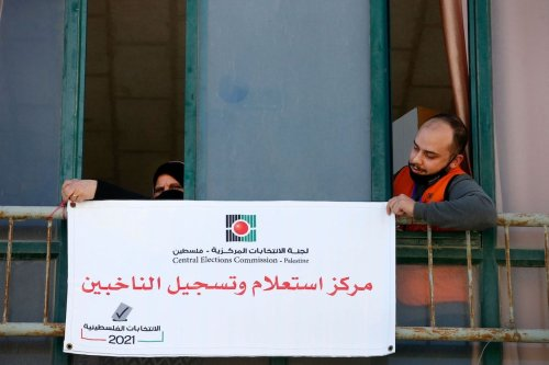 "Members of the Palestinian Central Elections Commission hang a sign reading in Arabic ""voter information and registration centre"" in the West Bank town of Hebron on 10 February 2021. [HAZEM BADER/AFP via Getty Images]"
