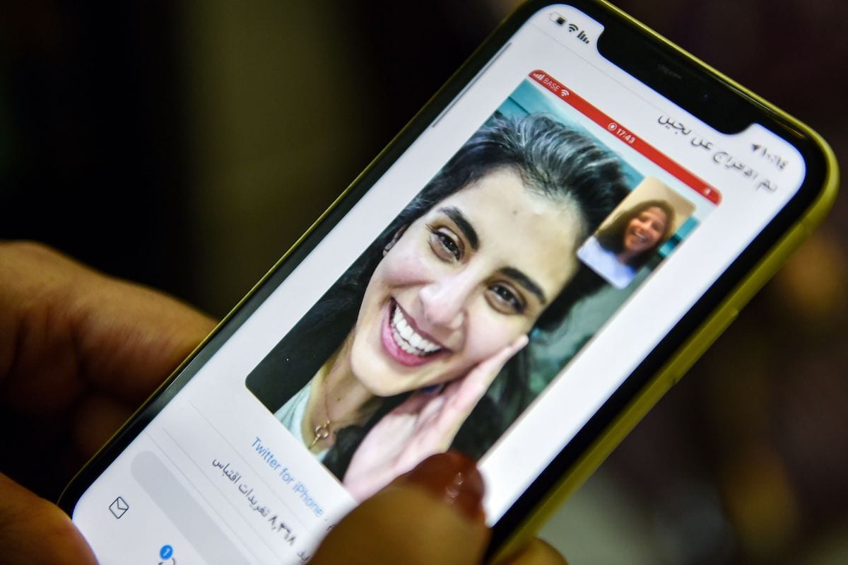 This picture taken February 10, 2021 in Saudi Arabia's capital Riyadh shows a woman viewing a tweet posted by the sister of Saudi activist Loujain al-Hathloul, Lina, showing a screenshot of them having a video call following Hathloul's release after nearly three years in detention. [FAYEZ NURELDINE/AFP via Getty Images]