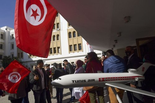 Employees of the Tunisian national airline Tunisair, wave national flags and shout anti-government slogans as they gather in front of the company's headquarters in the capital Tunis, on 19 February 2021 [FETHI BELAID/AFP via Getty Images]