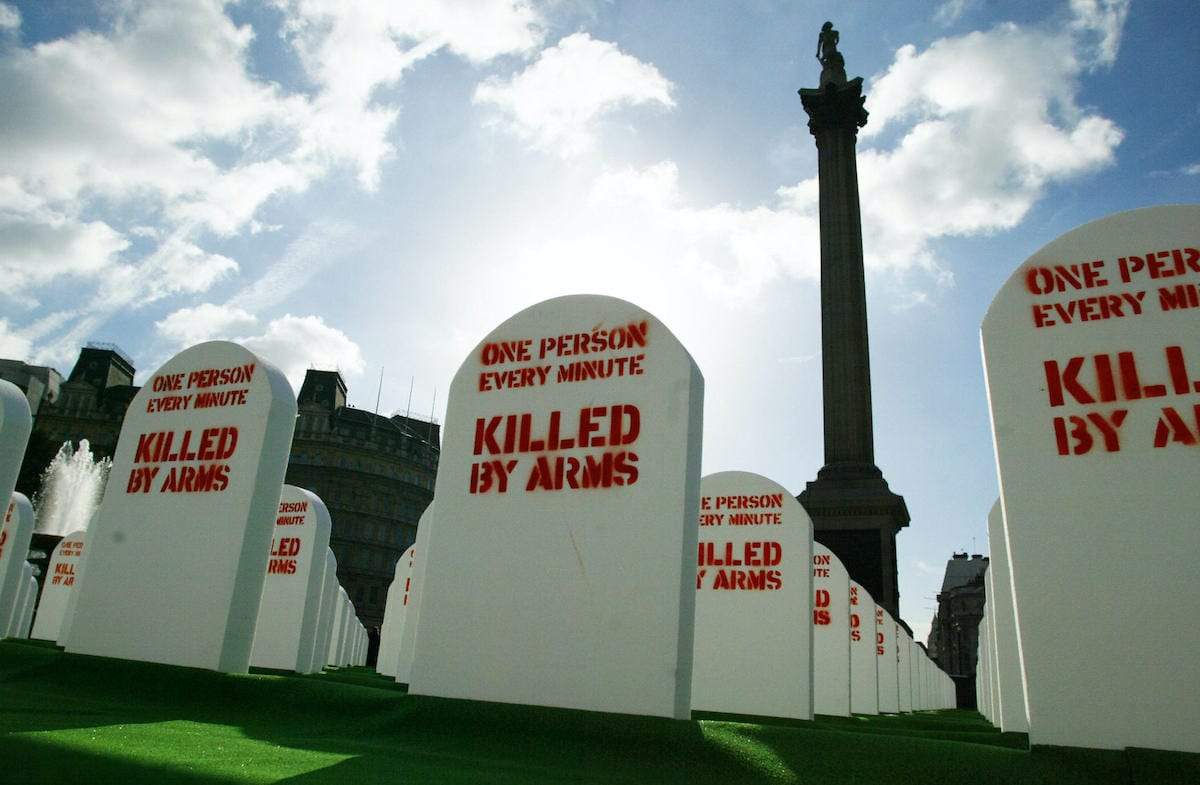Mock grave stones lie in a life-sized graveyard set up in Trafalgar Square, central London, 09 October 2003 by Amnesty International and the British humanitarian group Oxfam to represent the more than half a million people on average killed with conventional, light weapons every year. [JIM WATSON/AFP via Getty Images]