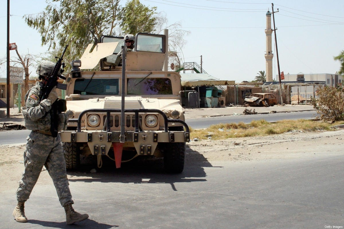A US soldier from Troop A, 8th Squadron of the 10th Cavalry, patrols through the neighbourhood of Amiriyah in western Baghdad, 24 July 2006 [AFP via Getty Images]