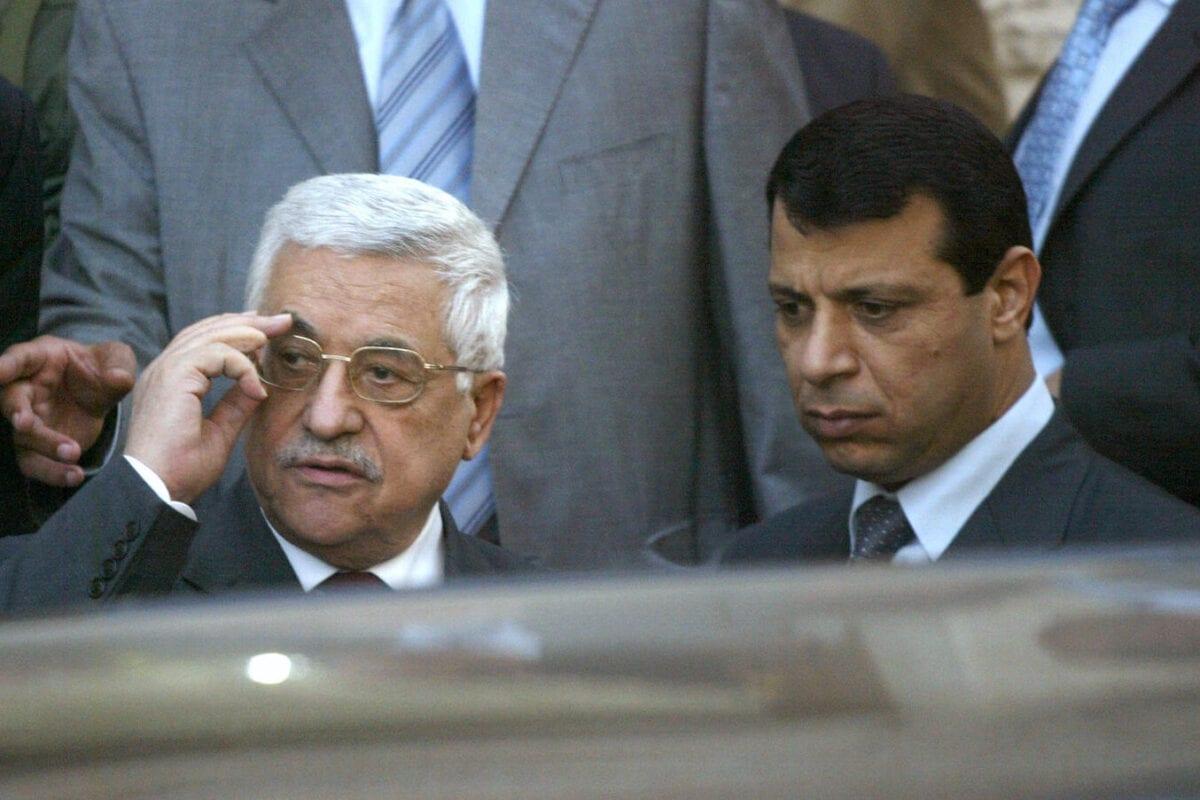 Palestinian President Mahmud Abbas (L) stands with Mohammad Dahlan, a strongman from the Fatah party, as they watch US Secretary of State Condoleezza Rice leave the Palestinian Authority headquarters or Muqataa in the West Bank city of Ramallah on 25 March 2007. [JAMAL ARURI/AFP via Getty Images]