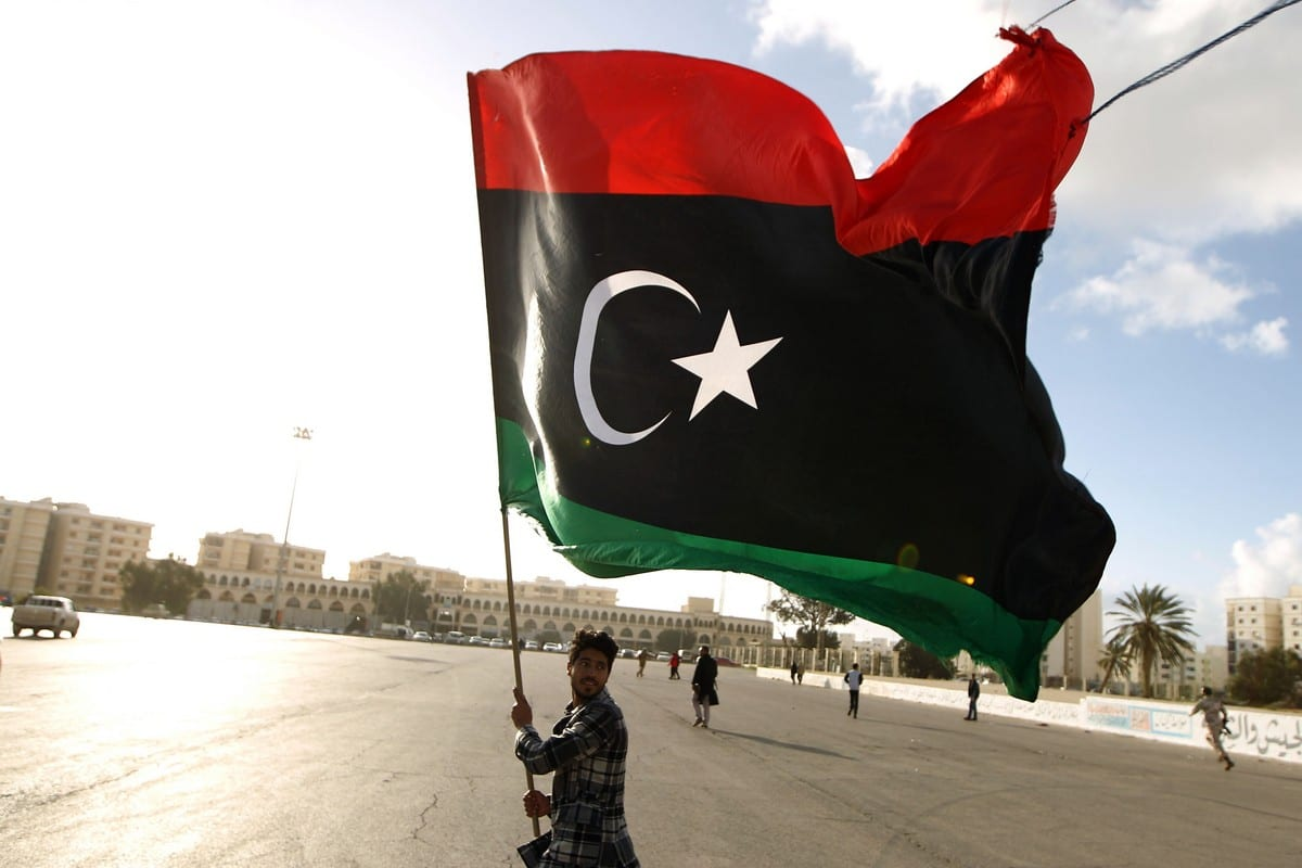 A Libyan man waves his national flag in Benghazi, Libya on 27 February 2015 [ABDULLAH DOMA/AFP/Getty Images]