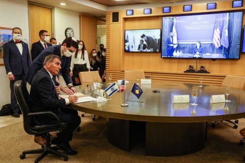 Israel's Foreign Minister Gabi Ashkenazi (L) signs a joint declaration establishing ties with Kosovo during an official ceremony held over Zoom with his counterpart from Kosovo Meliza Haradinaj Stublla (screen), at the Israeli Foreign Ministry headquarters in Jerusalem on February 1, 2021 [MENAHEM KAHANA/AFP via Getty Images]