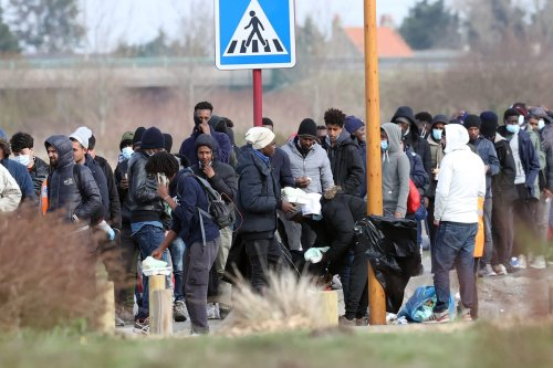 Irregular migrants are seen as they wait in a line to receive food aid in Calais, France on February 25, 2021 [Dursun Aydemir/Anadolu Agency]