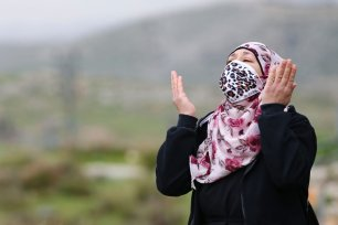 A woman reacts as Israeli-run Jerusalem Municipality team along with Israeli soldiers and bulldozers demolish the house owned by a disabled Palestinian Hatim Abu Rayala, near the al-Issawiya neighborhood claiming that it was unlicensed, in East Jerusalem on 1 March 2021. [Mostafa Alkharouf - Anadolu Agency]
